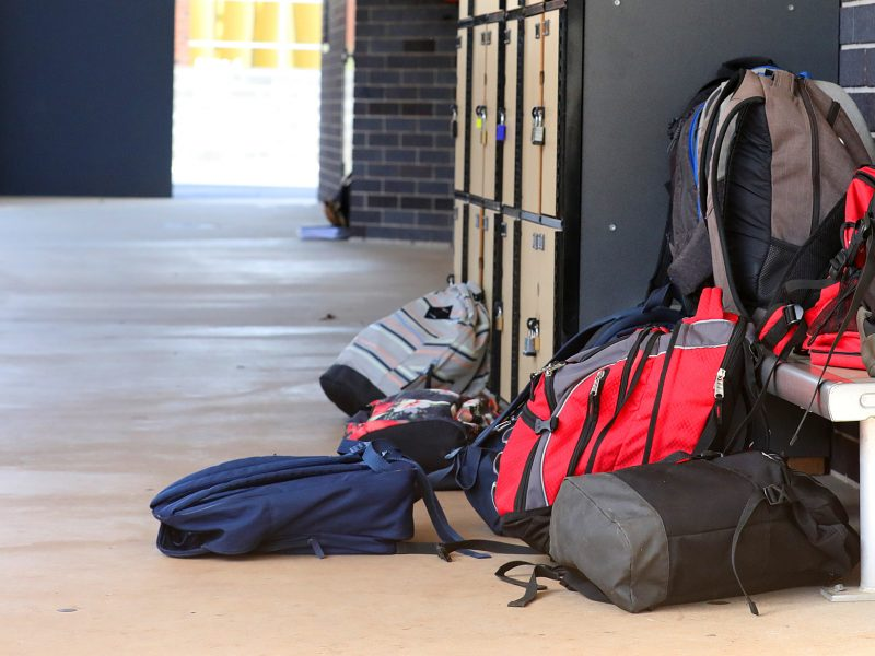 single and multiple school bags on seats and tables outside the class room. School educational facility and environment images